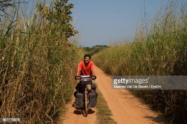 Man Riding Bicycle On Dirt Road