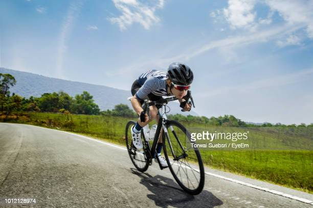 man riding bicycle on road against sky - torwai stock pictures, royalty-free photos & images