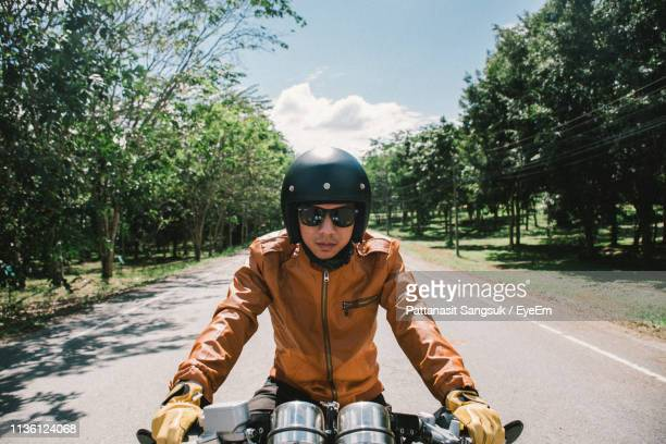man riding bicycle on road against trees - crash helmet stock pictures, royalty-free photos & images