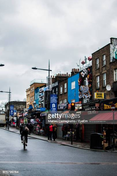 man riding bicycle on road by buildings - camden london stock pictures, royalty-free photos & images