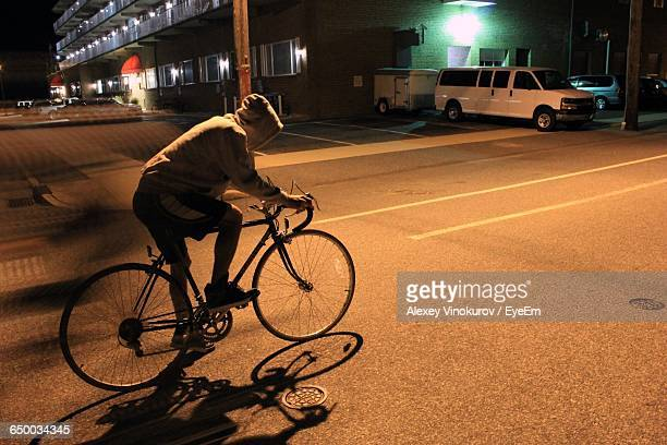 Man Riding Bicycle On Road In City At Night