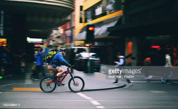 man riding bicycle on road in city - melbourne australia foto e immagini stock