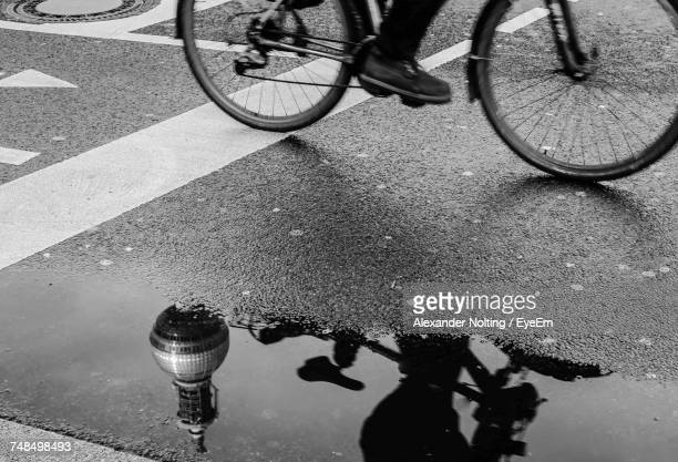 Man Riding Bicycle On Street By Puddle With Reflection Of Fernsehturm During Monsoon