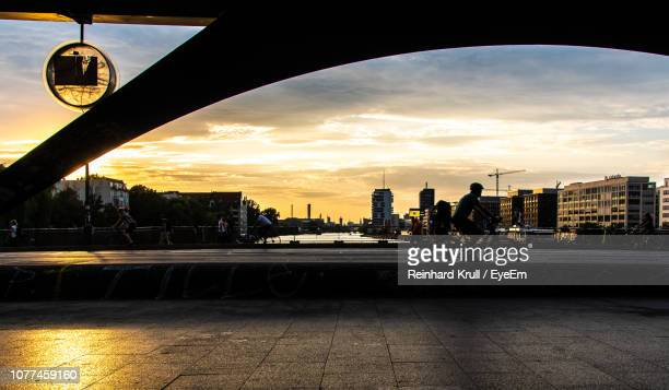 man riding bicycle on street in city - friedrichshain stock photos and pictures