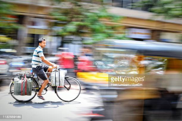 man riding bicycle on street in city - mumbai stock pictures, royalty-free photos & images