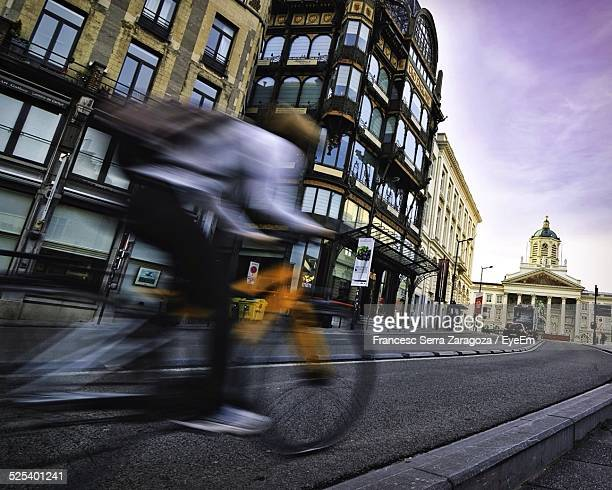 man riding bicycle on street - brussels capital region stock pictures, royalty-free photos & images