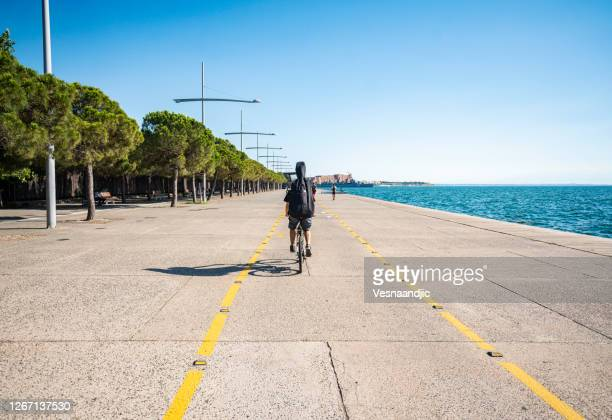 man riding bicycle on the promenade along the seaside - thessaloniki stock pictures, royalty-free photos & images