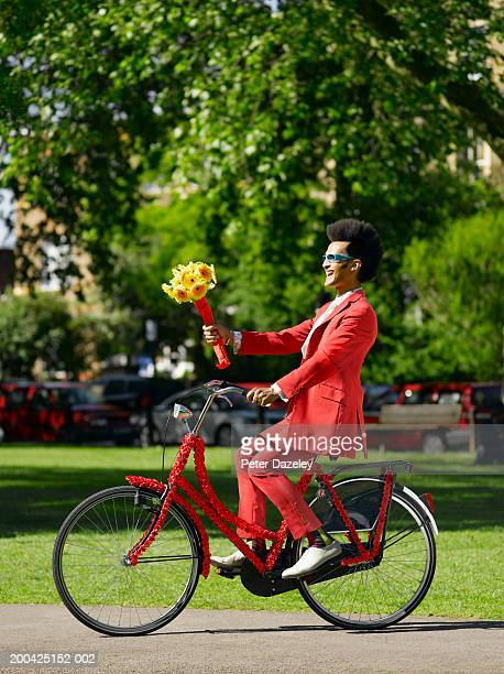 Man riding bicycle whilst holding bunch of gerberas, side view