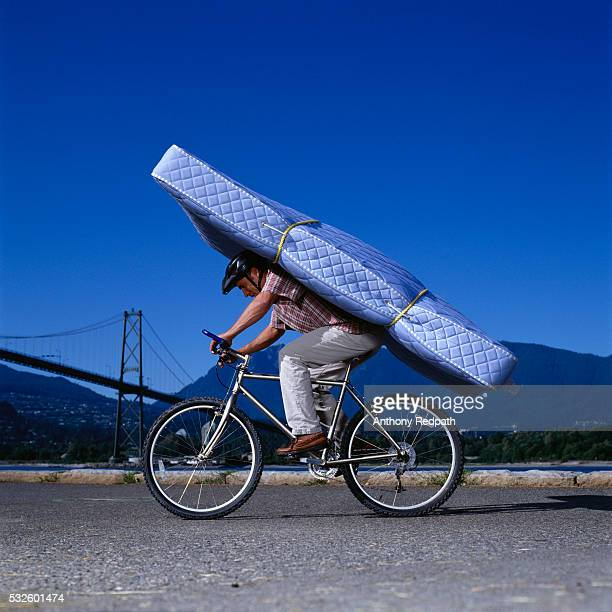 man riding bicycle with mattress on back - velo humour photos et images de collection