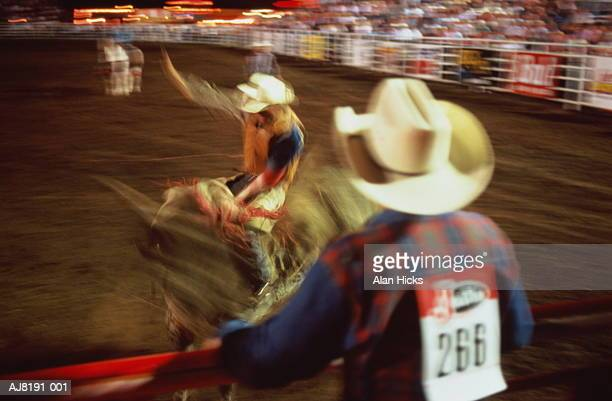 Man riding bull at rodeo, blurred action