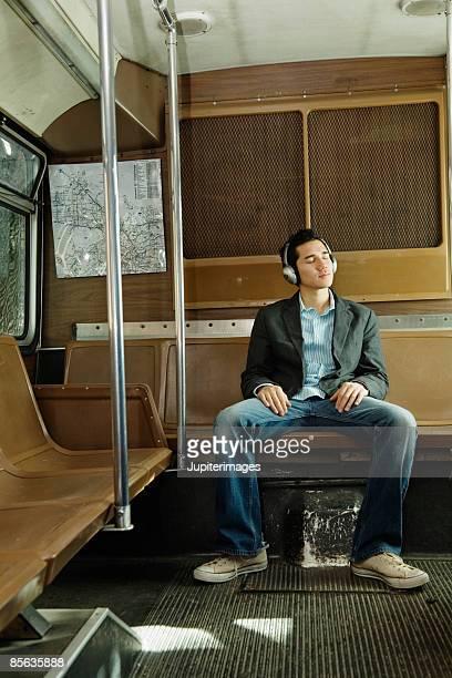 Man riding bus wearing headphones