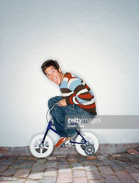 man riding child's bicycle with stabilisers, mouth open, portrait - velo humour photos et images de collection