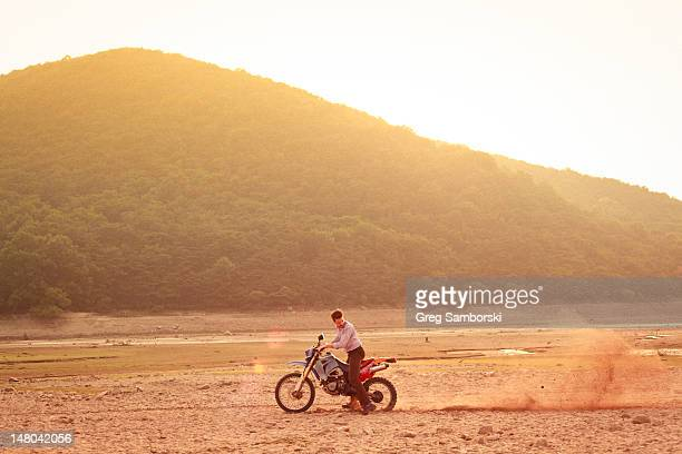 man riding dirt-bike in dress shirt and pants - northern european stock pictures, royalty-free photos & images