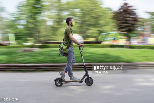 man riding e-scooter - electric scooter stock pictures, royalty-free photos & images