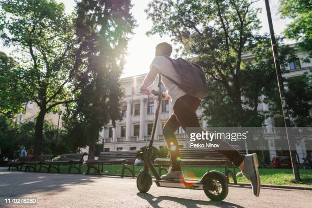 man riding e-scooter through the city park - electric scooter stock pictures, royalty-free photos & images