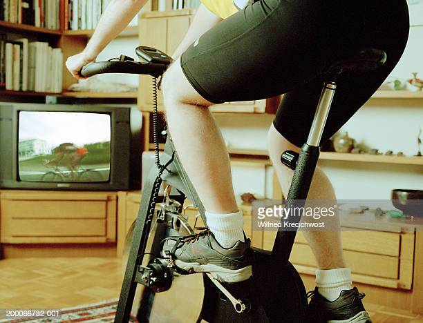 Man riding exercise bike, watching cyclist on television, low section