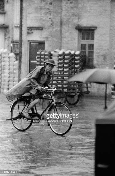 A man riding his bicycle in the rain in February 1979 in Canton aka Guangzhou China