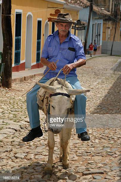 Man riding his donkey up a street in Trinidad, Cuba. Horses and donkeys may not be as usual than cars - but on the other hand there aren't that many...