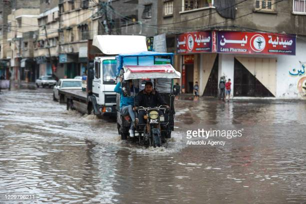 A man riding his motor vehicle makes his way through a flooded street caused by rainfall in Gaza City Gaza on November 26 2020