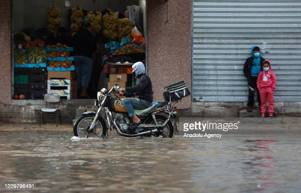 A man riding his motorcycle makes his way through a flooded street caused by rainfall in Gaza City Gaza on November 26 2020