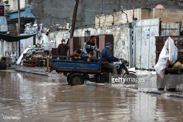 A man riding his vehicle makes his way through a flooded street caused by rainfall in Gaza City Gaza on November 26 2020