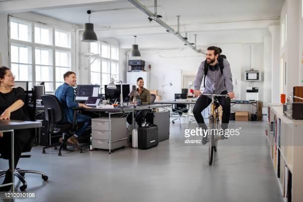 mens die huis op een fiets van bureau berijdt - aankomst stockfoto's en -beelden