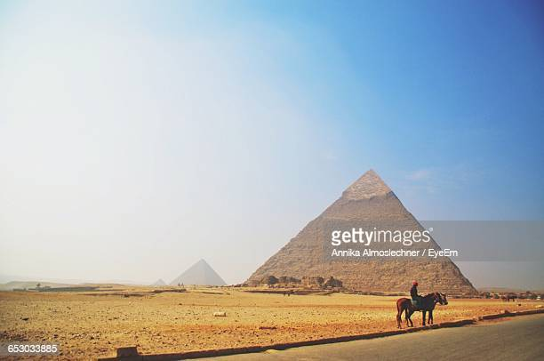 Man Riding Horse By Great Pyramid Of Giza Against Sky