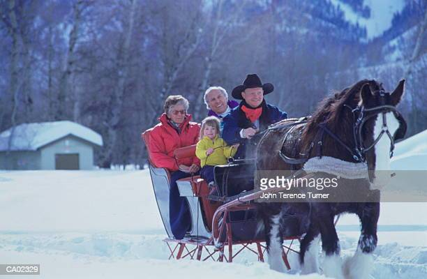 Man riding horse drawn sleigh with mature couple and girl (3-5)