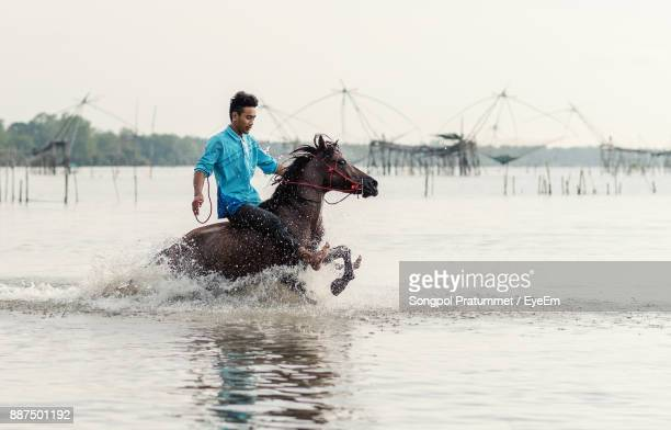 Man Riding Horse In Lake Against Sky During Sunset
