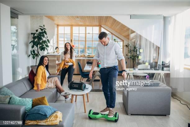 mens die hoverboard thuis in de woonkamer berijdt - hoverboard stockfoto's en -beelden