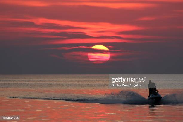 Man Riding Jet Boat On Sea Against Sky During Sunset