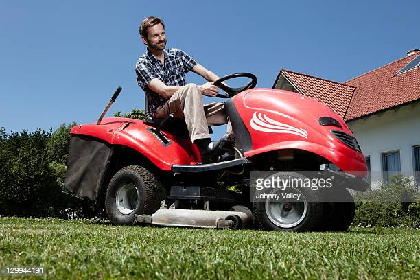 Man riding lawn mower in backyard