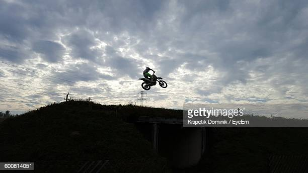 Man Riding Motorcycle In Mid-Air Over Field Against Cloudy Sky