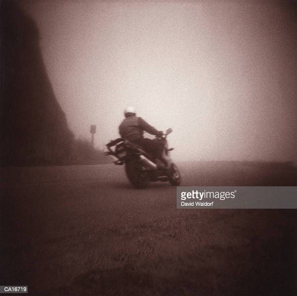 Man riding motorcycle on curving road (soft focus, toned B&W)
