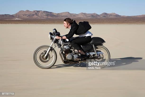 Man riding motorcycle on desert dry lake.