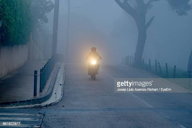 Man Riding Motorcycle On Road In Foggy Weather