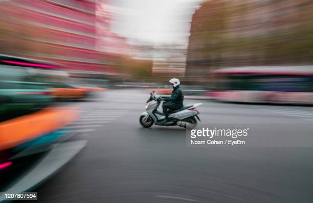 man riding motorcycle on road - noam cohen stock pictures, royalty-free photos & images