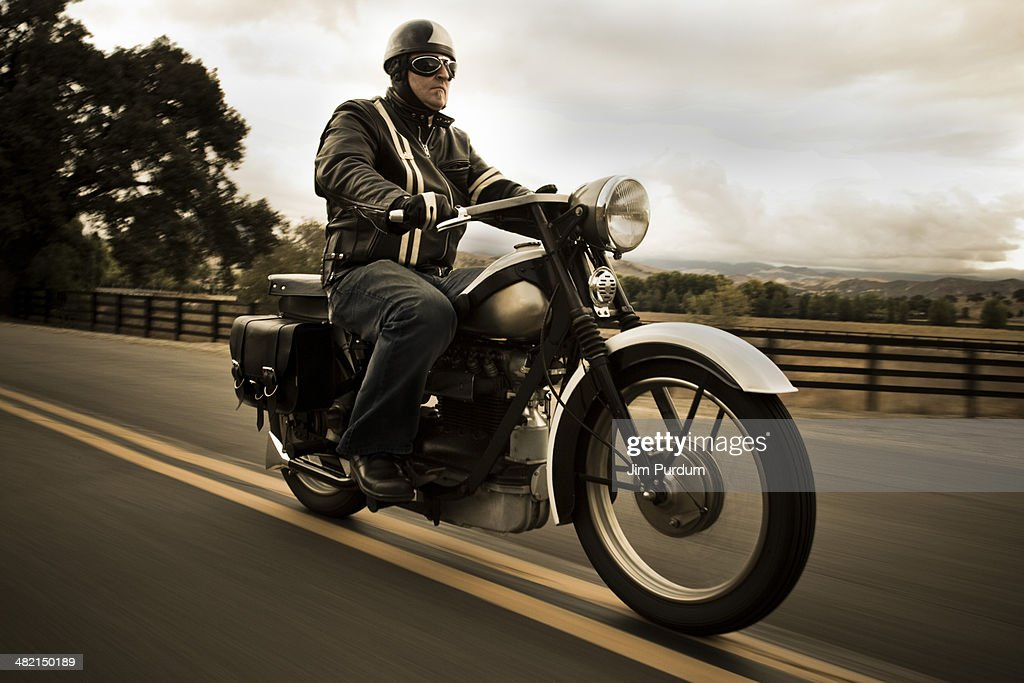 Man riding motorcycle on rural road : Stock Photo