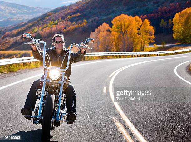 Man riding motorcycle on windy road in autumn.