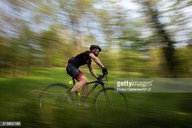 Man riding mountain bike in nature in the Bologna countryside, Italy