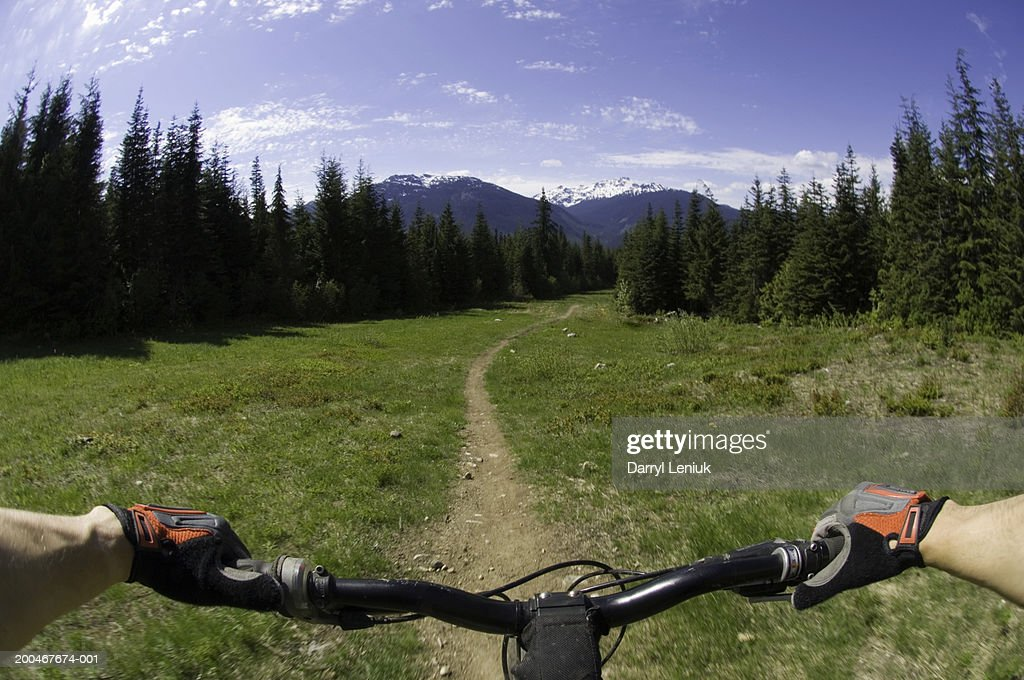 Man riding mountain bike on dirt footpath, mountains in background : Stock Photo