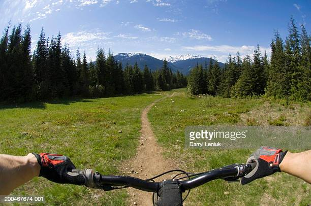 Man riding mountain bike on dirt footpath, mountains in background