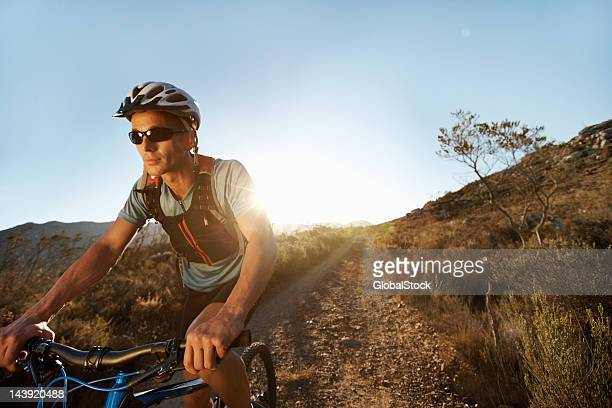 man riding mountain bike on gravel path - bicycle trail outdoor sports stock photos and pictures