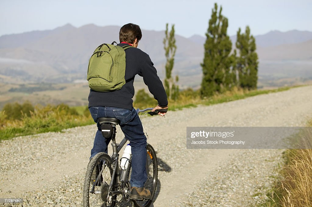Man Riding Mountain Bike On Road Stock Photo | Getty Images