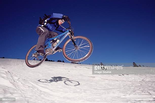 Man riding mountain bike on snow