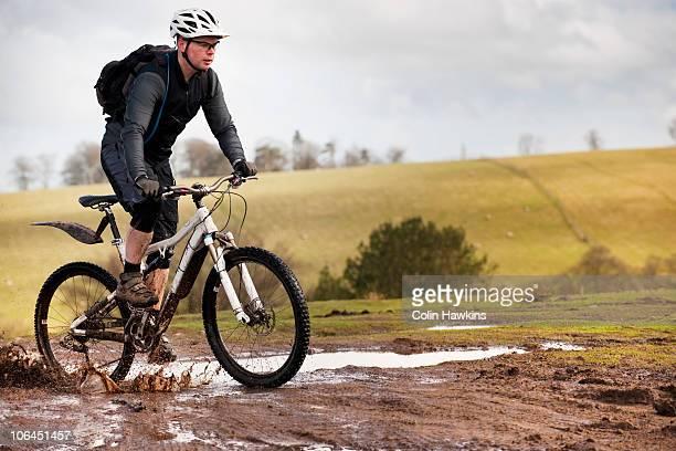 Man riding mountain bike through mud