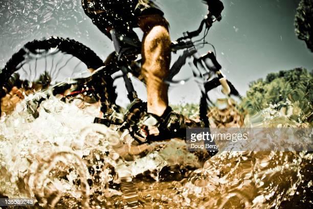 Man riding mountain bike through water