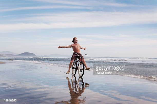 Man riding 'no hands' on a bike at the beach