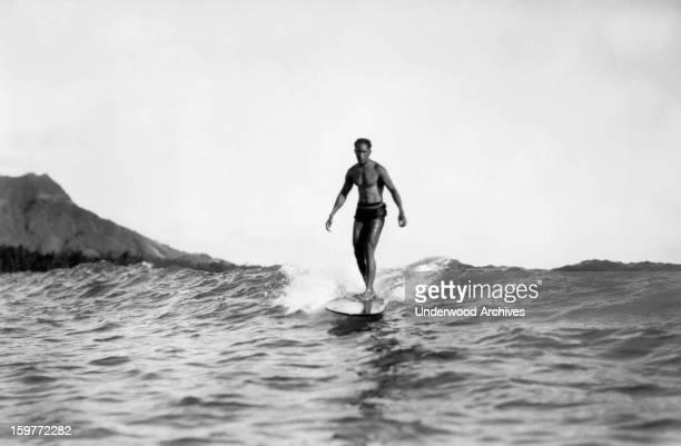 A man riding on a surfboard at Waikiki Beach with Diamond Head in the background Honolulu Hawaii 1929 He is possibly Duke Kahanamoku