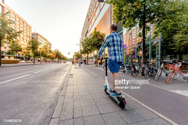 man riding on electric push scooter on the streets of berlin, germany - weitwinkelaufnahme stock-fotos und bilder